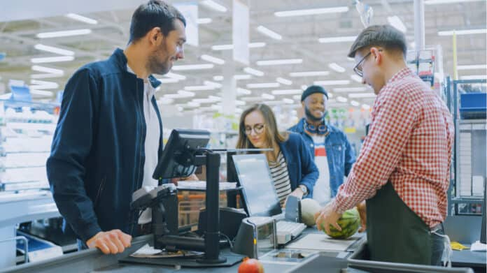 At the Supermarket: Checkout Counter Professional Cashier Scans Groceries and Food Items